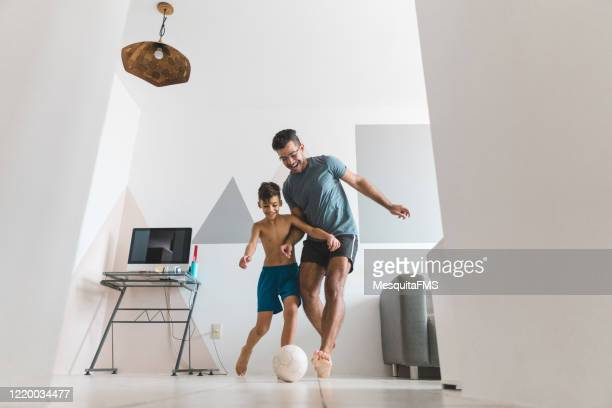 father and son playing soccer in the living room - giochi per bambini foto e immagini stock