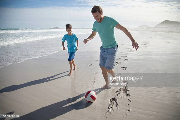 Father and son playing soccer on beach