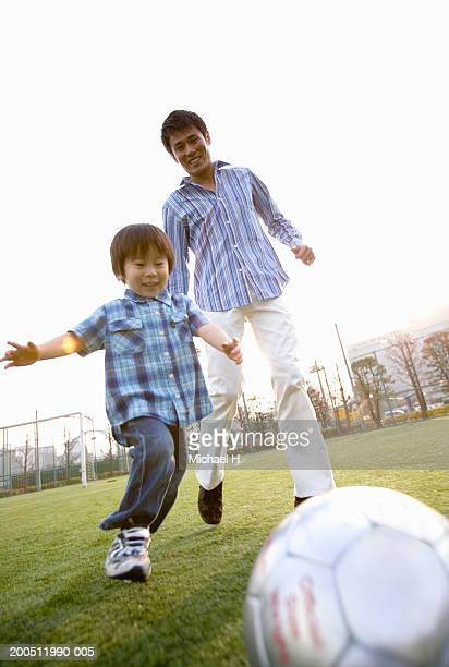 Father and son (2-4) playing soccer on sports field