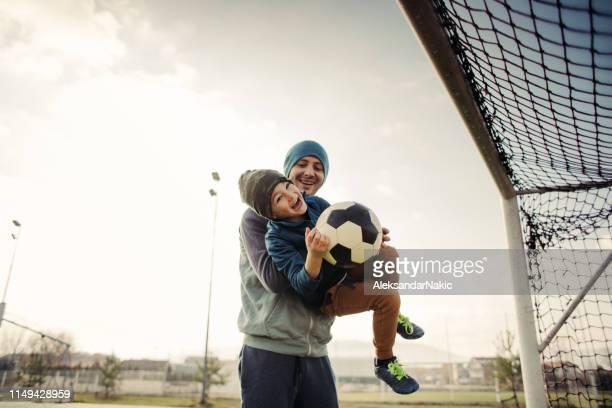 vader en zoon voetbal buitenshuis - voetbalcompetitie sportevenement stockfoto's en -beelden
