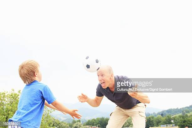 Father and son playing soccer outdoors