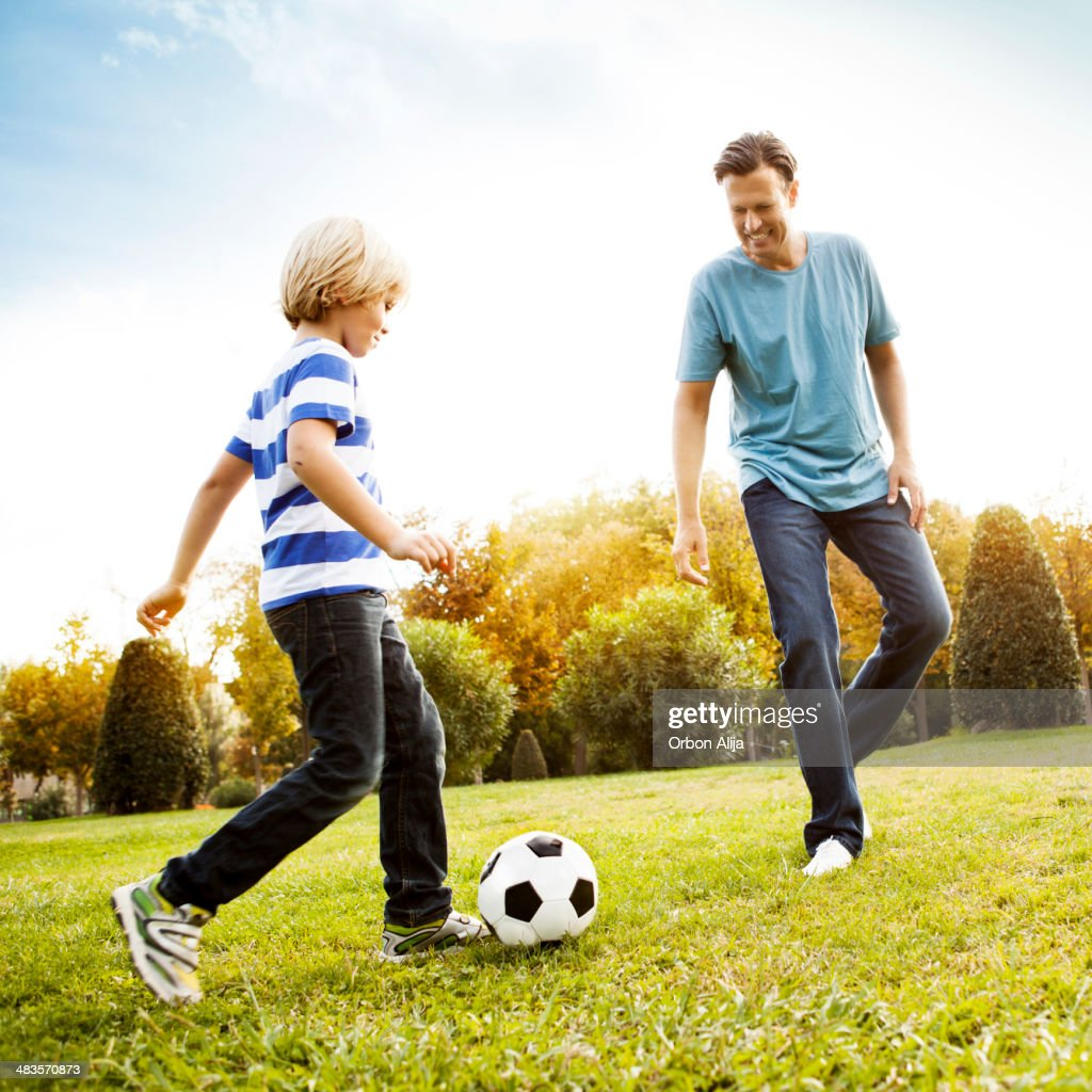 Father and son playing soccer : Stock Photo
