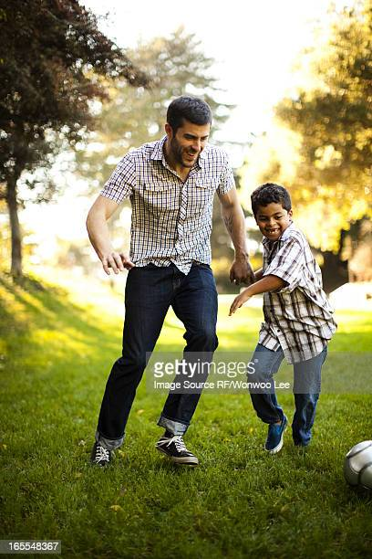 Father and son playing soccer together