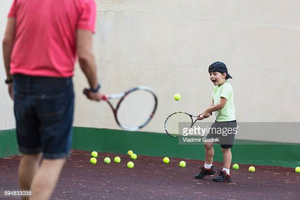 Father and son playing tennis on field