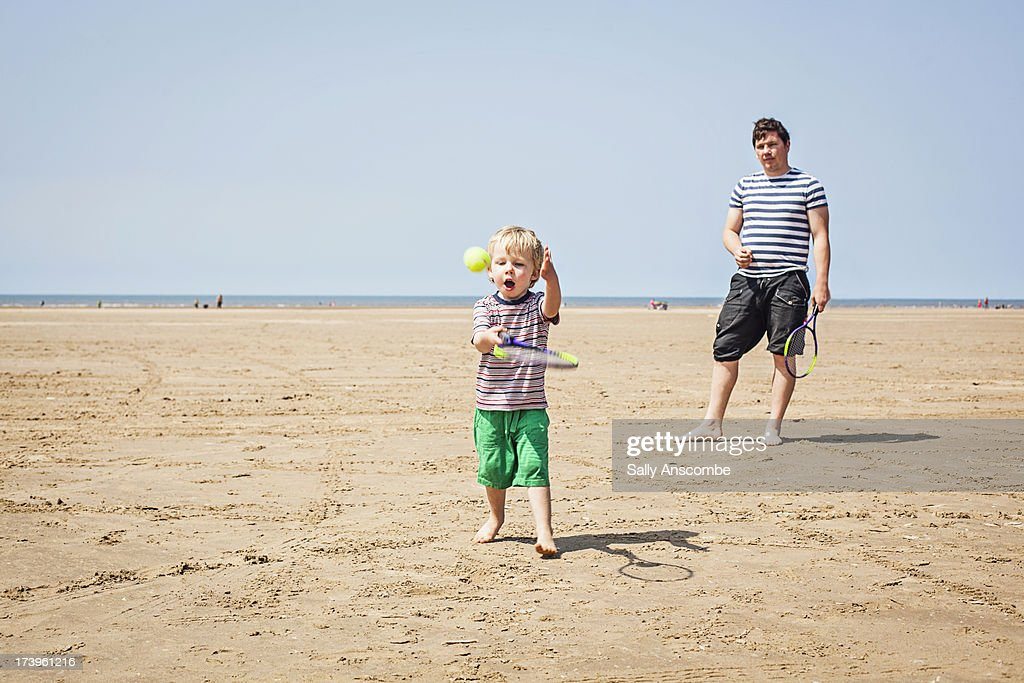Father and son playing tennis on the beach : ストックフォト