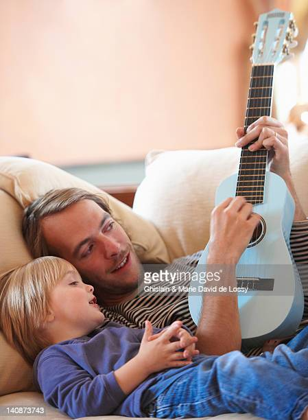 father and son playing ukulele - saint ferme stock photos and pictures