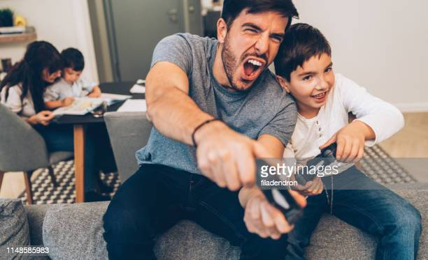father and son playing video game - handheld video game stock pictures, royalty-free photos & images