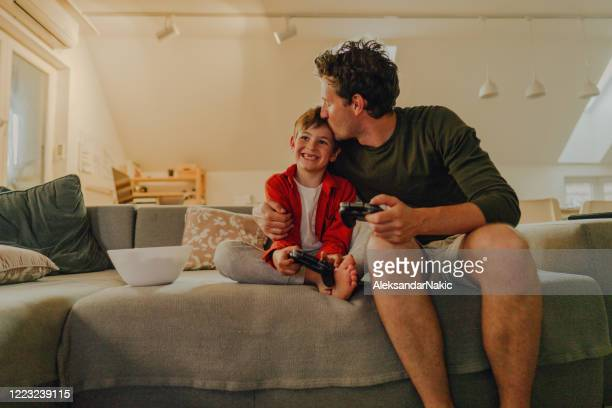 father and son playing video games at home - simple living stock pictures, royalty-free photos & images