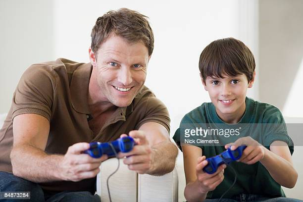Father and son (10-11 years) playing video games
