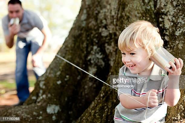 Vater und Sohn spielen Telefon im park