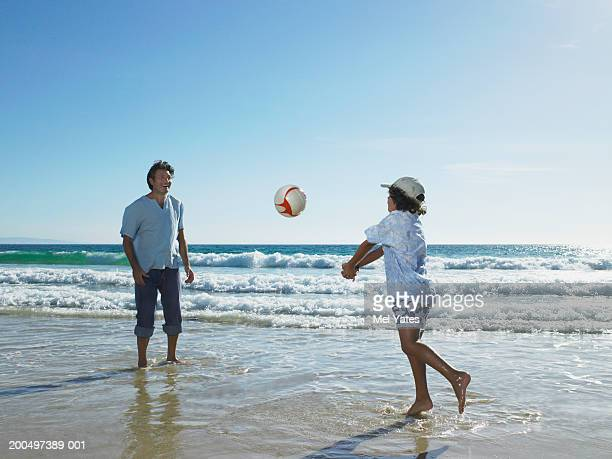 father and son (9-11) playing with ball on beach, outdoors - beach volley foto e immagini stock
