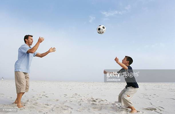Father and son (12-13 years) playing with ball on beach, side view