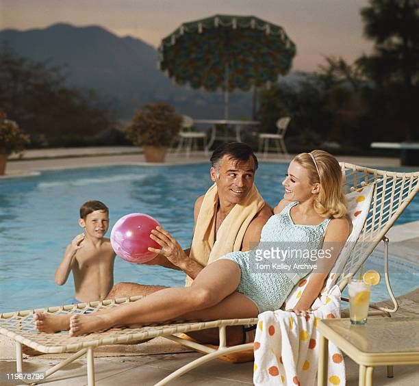 Father and son playing with beach ball while mother relaxing on lounge chair, smiling