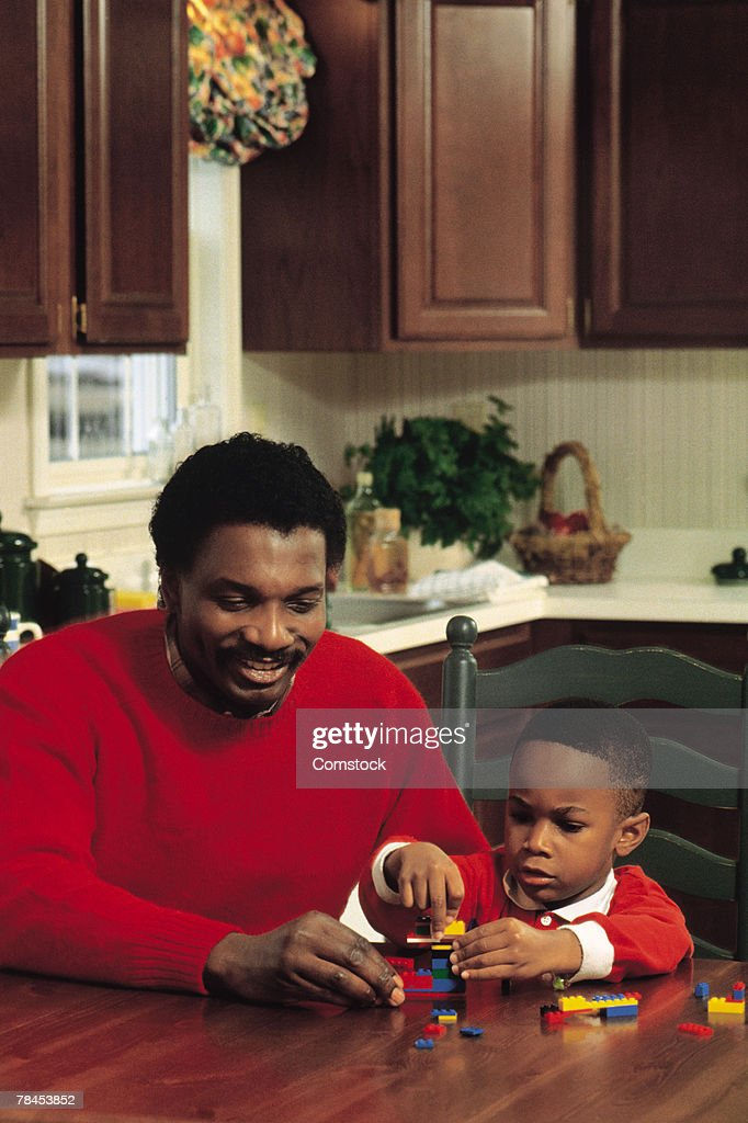 Father and son playing with blocks at kitchen table : Stockfoto