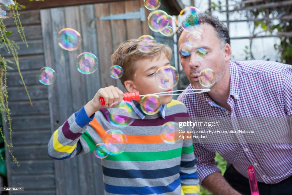 Father and son playing with bubbles on garden patio : Stock Photo