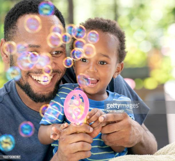 Father and Son Playing with Bubbles