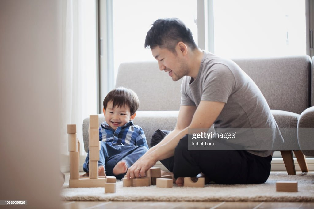 Father and son playing with building blocks together : Stock Photo