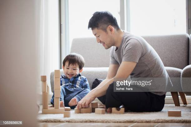 father and son playing with building blocks together - asian stock pictures, royalty-free photos & images