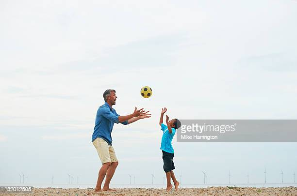 Father and son playing with football on beach.