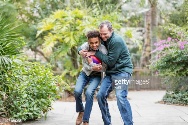 father and son playing with football - tackling stock pictures, royalty-free photos & images