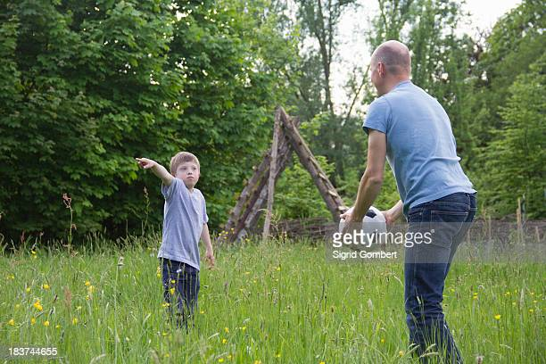 father and son playing with football - sigrid gombert stock-fotos und bilder