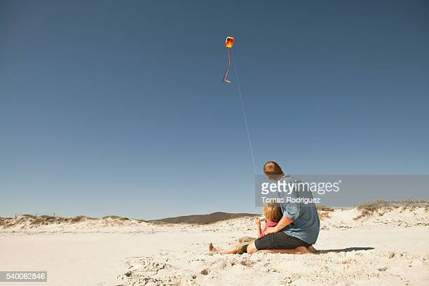 Father and son (6-7) playing with kite on sandy beach