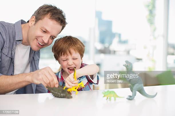 Père et fils jouant avec les dinosaures en plastique