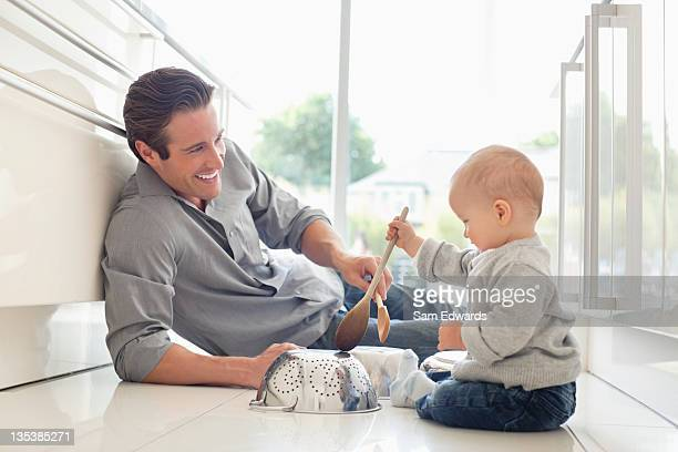 Father and son playing with pots and wooden spoons
