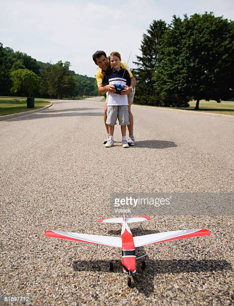 Father and son playing with remote control airplane