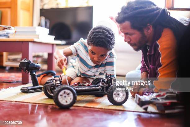 father and son playing with remote control car - genderblend stock pictures, royalty-free photos & images