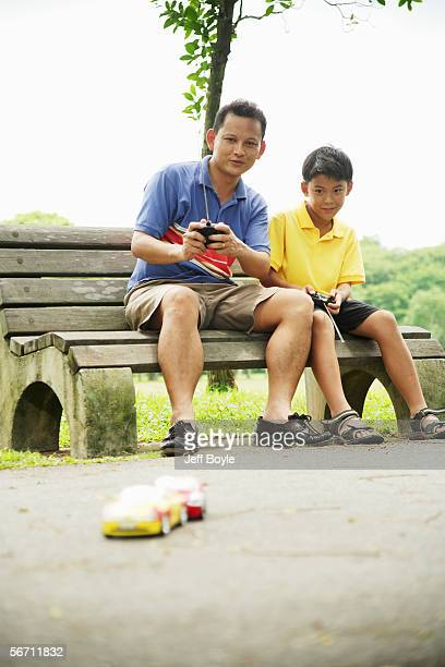 father and son playing with remote control cars in the park - remote control car games stock pictures, royalty-free photos & images