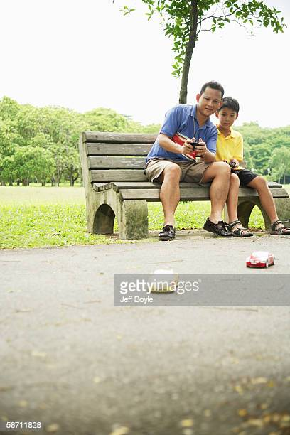 father and son playing with remote control cars - remote control car games stock photos and pictures