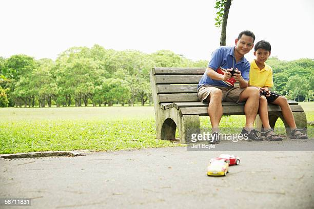 father and son playing with remote control cars - remote controlled car stock pictures, royalty-free photos & images
