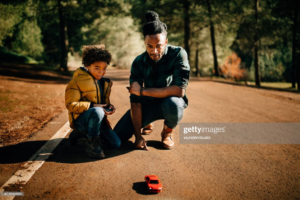 Father and son playing with remote controlled car in nature : Stock Photo