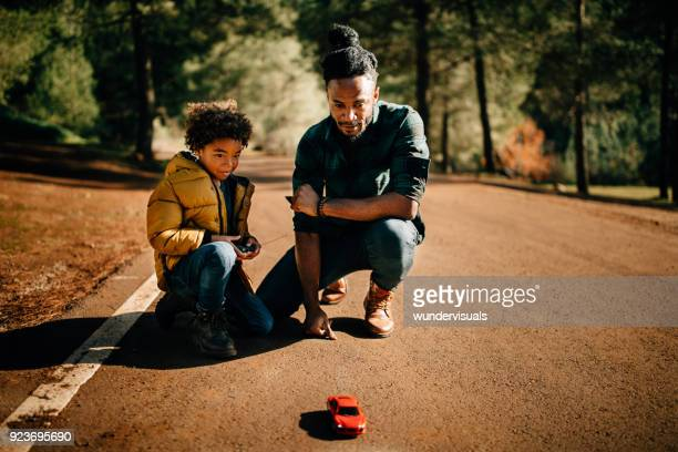 Father and son playing with remote controlled car in nature