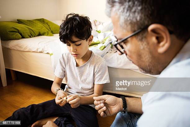 Father and son playing with rubber bands at home