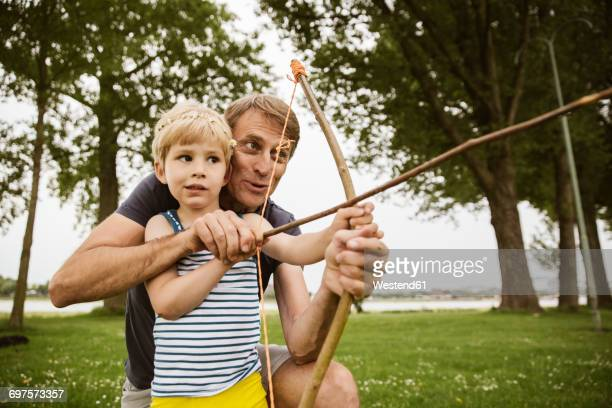 father and son playing with self made bow and arrow - arco arco e flecha - fotografias e filmes do acervo