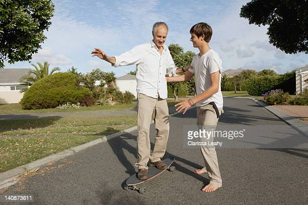 father and son playing with skateboard - teen boy barefoot stock photos and pictures