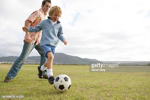 father and son (6-7 years) playing with soccer ball on field, low angle view - 6 7 years stock pictures, royalty-free photos & images