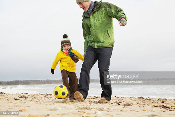 Father and son playing with soccer ball