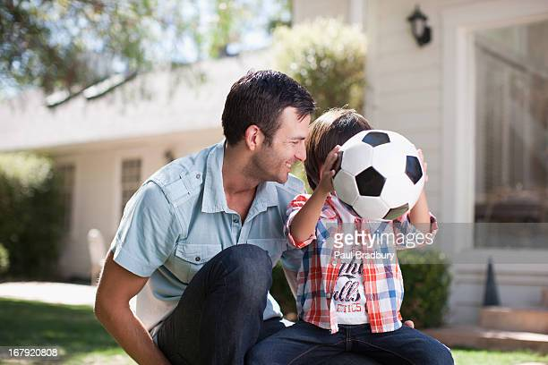 father and son playing with soccer ball - football bulge stock photos and pictures