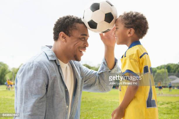 father and son playing with soccer ball - forehead stock pictures, royalty-free photos & images