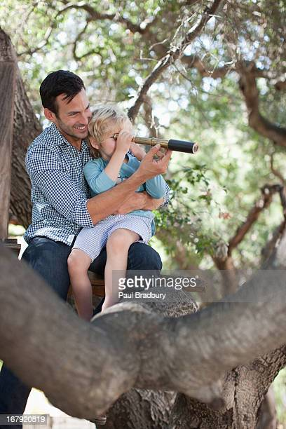 Father and son playing with telescope in tree