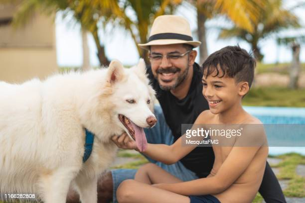 Father and son playing with their dog