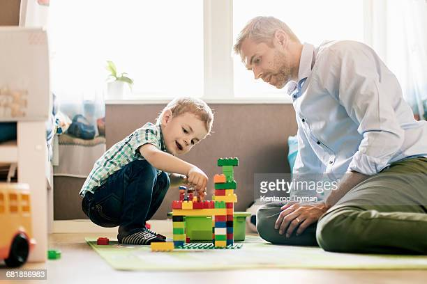 father and son playing with toy blocks while sitting at home - toy block stock pictures, royalty-free photos & images