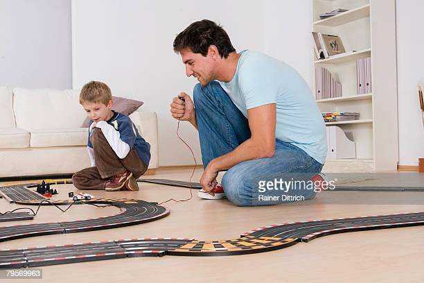 Father and son playing with toy racetrack