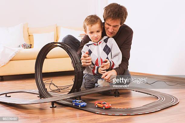Father and son (4-5) playing with toy racetrack