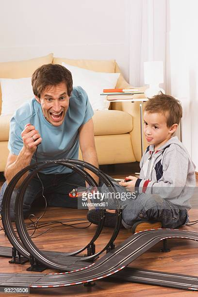 Father and son (4-5) playing with toy racetrack, smiling
