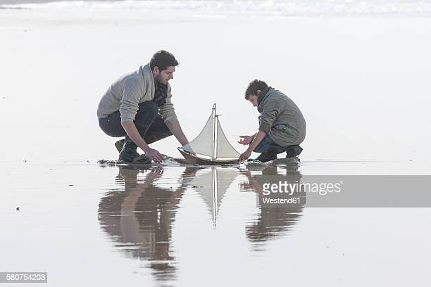 Father and son playing with toy sailing boat at seafront