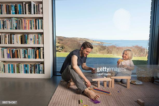 Father and son playing with wooden blocks at home